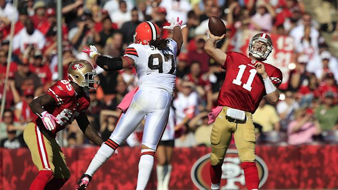 San Francisco 49ers quarterback Alex Smith (11) passes as Cleveland Browns defensive end Jabaal Sheard (97) applies pressure in the second quarter of an NFL football game in San Francisco, Sunday, Oct. 30, 2011. Also pictured at left is 49ers tight end Vernon Davis (85). (AP Photo/Marcio Jose Sanchez)