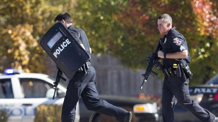 Police and swat team members respond to a call of a shooting at the Azana Spa in Brookfield, Wis.  Sunday,Oct. 21, 2012.  Multiple people were wounded when someone opened fire at the spa near the Brookfield Square Mall. Deputies are still looking for the gunman. (AP Photo/Tom Lynn)