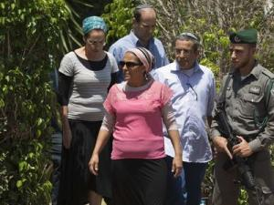 Parents of missing Israeli teens Eyal, Gil-Ad and Naftali, walk outside the Shaer family home in Talmon