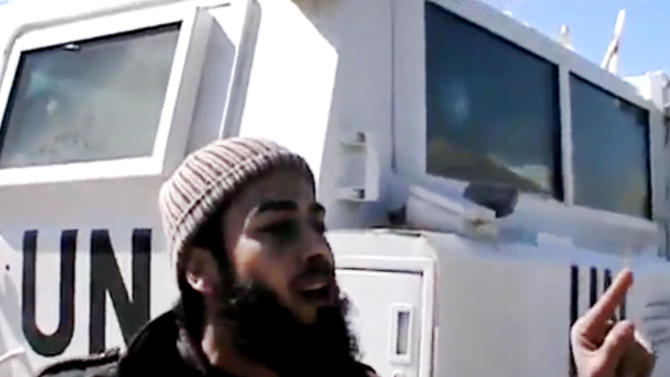 In this Wednesday, March 6, 2013 image taken from video obtained from the Ugarit News, which has been authenticated based on its contents and other AP reporting, a Free Syrian Army fighter stands next to United Nations Disengagement Observer vehicle near Golan Heights in the southern province of Daraa, Syria. Clashes between Syrian troops and rebel fighters flared on Thursday near an area where armed fighters linked to the opposition abducted 21 U.N. peacekeepers a day earlier. In an online video, a man identified as a spokesman for the Martyrs of Yarmouk Brigades said his group will hold the peacekeepers until Assad's forces withdraw from Jamlah. (AP Photo/Ugarit News via AP video)