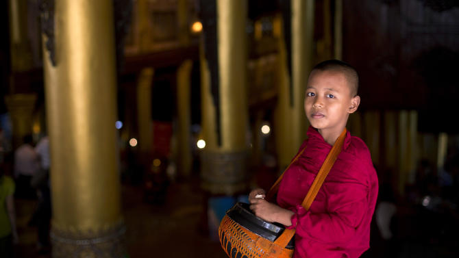In this picture taken on Thursday, Nov. 15, 2012, a novice Buddhist monk walks expecting alms at Shwedagon Pagoda in Yangon, Myanmar. Word of U.S. President Barack Obama's historic visit has spread quickly around Yangon, which is readying itself with legions of hunched workers painting fences and curbs, pulling weeds and scraping grime off old buildings in anticipation of the president's Monday arrival. (AP Photo/Gemunu Amarasinghe)