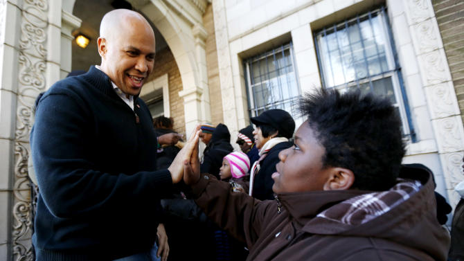 FILE - In this Friday, Nov. 9, 2012 file photo, Newark Mayor Cory Booker, left, greets 13-year-old Blonbzell Taylor outside of Clinton Hill Community Resource Center, where residents impacted by Superstorm Sandy received clothing donations in Newark, N.J. On Thursday, Nov. 29, 2012, Booker said he will live on food stamps for a week starting Tuesday, Dec. 4, 2012, honoring a challenge he made to a Twitter follower earlier in the month. He said he will be limited to $1.40 for each meal. (AP Photo/Julio Cortez)