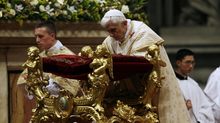 Pope Benedict XVI kneels as he celebrates the Christmas Eve Mass in St. Peter's Basilica at the Vatican, Monday, Dec. 24, 2012. (AP Photo/Gregorio Borgia)