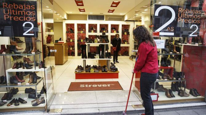 Women look at shoes inside a store as a worker sweeps the street outside, in Madrid