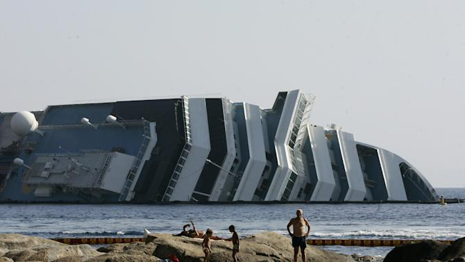 "Tourists relax on rocks in front of the Costa Concordia wreckage on the Giglio Island, Italy, Thursday, July 12, 2012. Works have begun to remove the tons of rocky reef embedded into the Concordia cruise ship's hull, a first step in plans to eventually tow the wreck away from the island, where it ran aground last January. The whole removal process could take as long as a year. In a broadcast interview Tuesday, Concordia's captain Francesco Schettino described the collision as a ""banal accident"" in which ""destiny"" played a role. (AP Photo/Gregorio Borgia)"