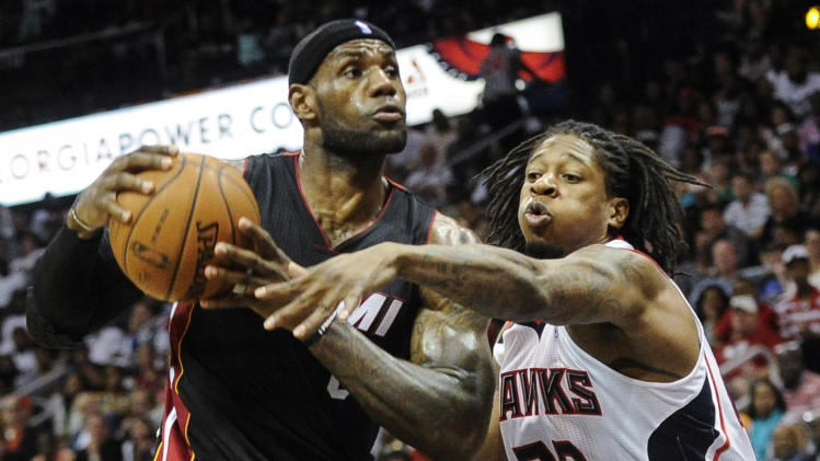 Miami Heat forward LeBron James, left, tries to keep the ball away from the defense of Atlanta Hawks forward Cartier Martin (20) during the second half of an NBA basketball game on Saturday, April 12, 2014, in Atlanta. Atlanta won 98-85. (AP Photo/John Amis)