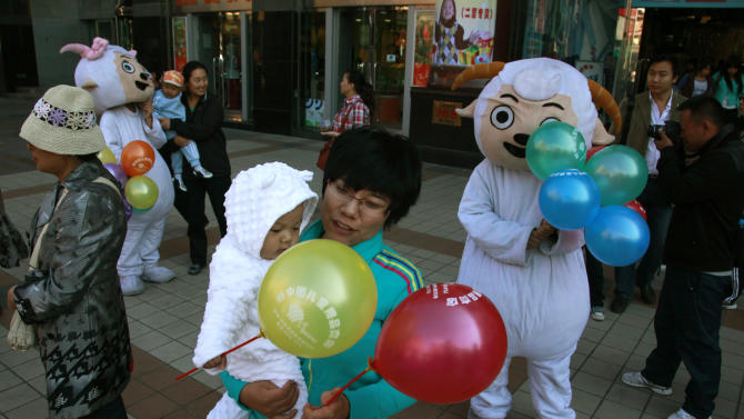 """In this photo taken Sunday, Oct. 2, 2011, Chinese women and children gather near mascots of characters from the cartoon """"Pleasant Goat and Big Big Wolf"""" on a street in Beijing, China. A Chinese court has ruled the producer of the hit kids cartoon was partly to blame for the injuries suffered by two children when their friend tied them to a tree and set them on fire in an imitation of a scene from the show, state media reported Wednesday, Dec 18, 2013. (AP Photo/Ng Han Guan)"""