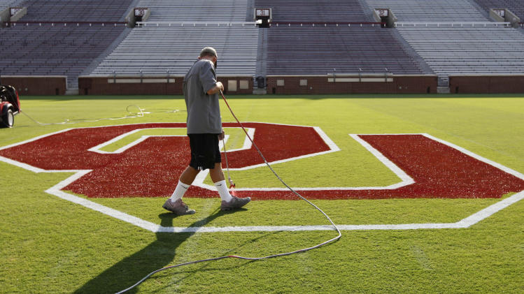 Cliff Brunken finishes up the U in the OU at the center of Owen Field at the University of Oklahoma in Norman, Okla., Wednesday, Aug. 31, 2011. Number one Oklahoma opens the season on Saturday against Tulsa. (AP Photo/Sue Ogrocki)