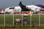 Airport staff work around a Thai Airways plane that skidded off the runaway while landing at Bangkok's Suvarnabhumi Airport September 9, 2013. REUTERS/Athit Perawongmetha