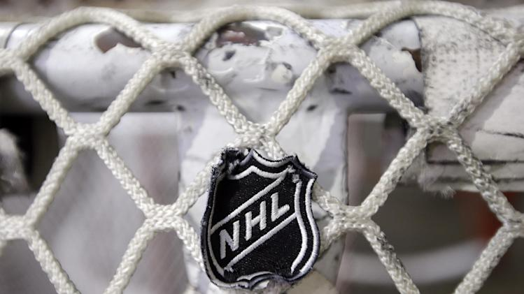FILE - In this file photo taken Sept. 17, 2012, the NHL logo is seen on a goal at a Nashville Predators practice rink in Nashville, Tenn. The NHL eliminated 16 more days from the regular-season schedule Monday, Dec. 10, 2012, and if a deal with the players' association isn't reached soon the whole season could be lost. The league wiped out all games through Dec. 30 in its latest round of cancellations. Negotiations between the league and the players' association broke off last week, but NHL deputy commissioner Bill Daly said Sunday the sides are trying to restart talks this week. (AP Photo/Mark Humphrey, file)