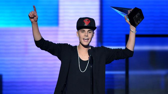 "Justin Bieber accepts the award for favorite album - pop/rock for ""Believe"" at the 40th Anniversary American Music Awards on Sunday, Nov. 18, 2012, in Los Angeles. (Photo by John Shearer/Invision/AP)"