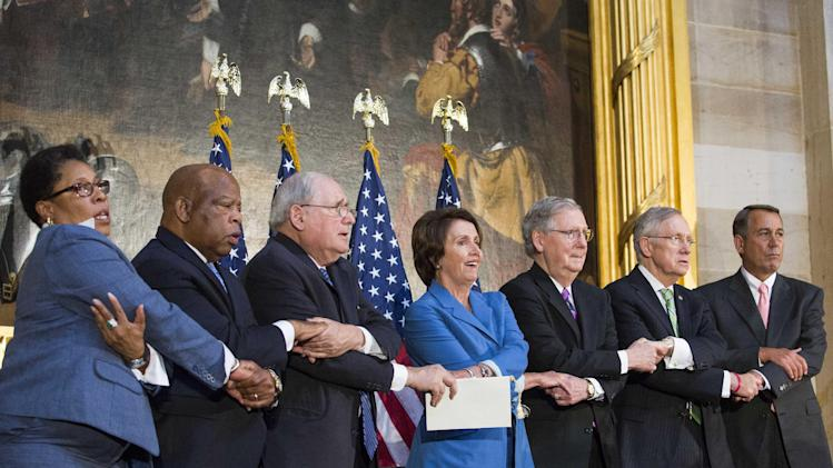 Representatives and Senators lock arms as they sing 'We Shall Overcome' during a ceremony to posthumously award the Congressional Gold Medal to Dr. Martin Luther King, Jr. and Coretta Scott King, on Capitol Hill, June 24, 2014 in Washington, DC