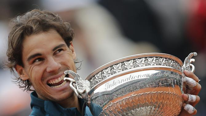 Spain's Rafael Nadal bites the trophy after winning against compatriot David Ferrer in three sets 6-3, 6-2, 6-3, in the final of the French Open tennis tournament, at Roland Garros stadium in Paris, Sunday June 9, 2013. (AP Photo/Christophe Ena)