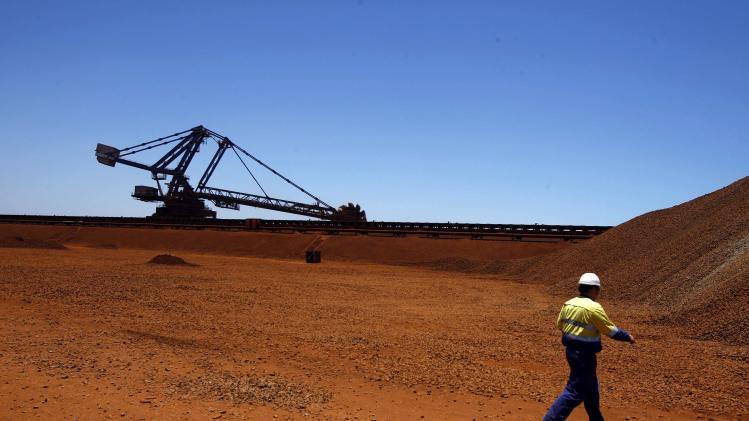 Worker walks past a bucket-wheel reclaimer at the Fortescue loading dock located at Port Hedland in the Pilbara region of Western Australia