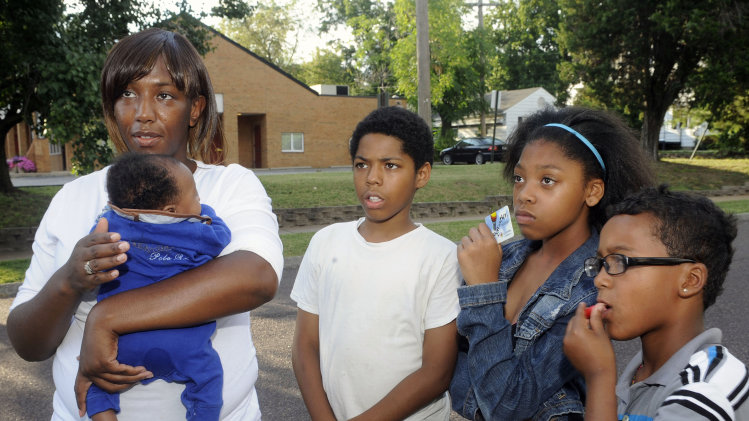 Christina Holmes, left, 29, of the Normandy Schood District in St. Louis County holds her infant Kerian, one month old, as she discusses the school transfer program in Normandy, Mo. standing next to three of her children, left to right, Daevion 12,, Amelian, 10, and Andrew, 8, Wednesday, Aug. 7, 2013. Christina's 14 year old son will attend school in the Francis Howell School District as part of the transfer program. (AP Photo/Bill Boyce)