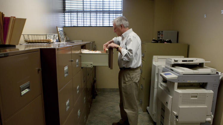 In this Feb. 15, 2012 photo, Steve Wyard, 61, a regional sales director of All Valley Washer Service, looks for files in his office in the Van Nuys section of Los Angeles. Wyard and his wife have two sons, 19 and 21, to put through college, and they see that pushing back retirement for several years. Until then Wyard plans to keep working. (AP Photo/Jae C. Hong)