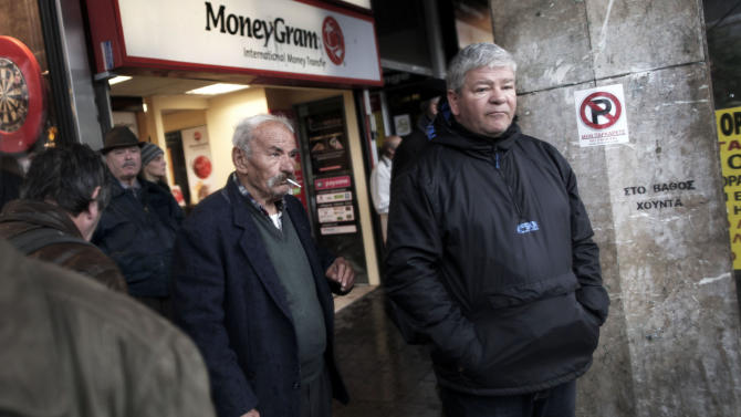 An elderly man smokes outside a money transfer office during a rainfall in central Athens, Tuesday, Dec. 18, 2012. Greece is failing to collect the tax it is owed and is in danger of missing key targets that need to be met to reduce the government's staggering debt pile, the European Union warned on Monday. (AP Photo/Petros Giannakouris)
