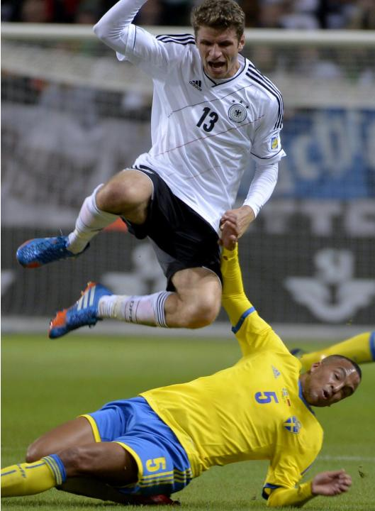 Germany's Thomas Muller jumps over Sweden's Martin Olsson during the 2014 World Cup group C qualifying soccer match between Sweden and Germany at Friends Arena in Stockholm, Sweden, on Tuesday Oct. 15