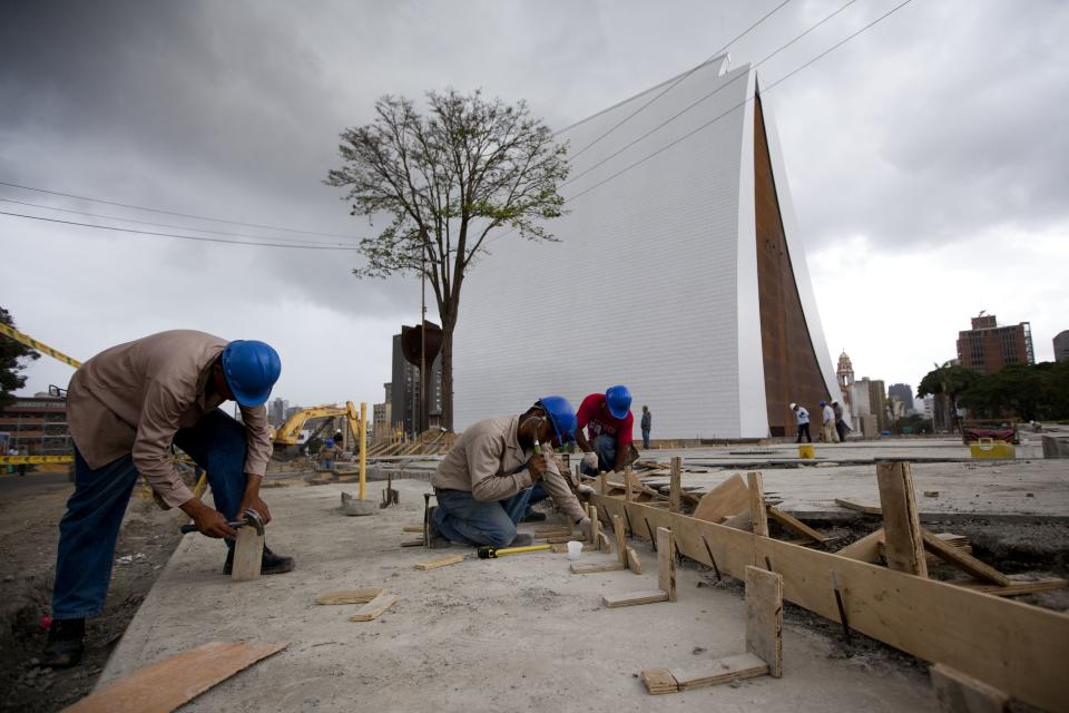 People work outside the Bolivar's Mausoleum white tower in Caracas, Venezuela, Monday, July 23, 2012. The 160-foot (50-meter) mausoleum is to be inaugurated in the coming days, though it is not quite finished. (AP Photo/Ariana Cubillos)