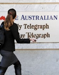 A woman walks past the entrance to the News Limited building in Sydney on June 20. Mining magnate Gina Rinehart laid down an ultimatum to the chairman of troubled Australia media giant Fairfax -- meet a number of performance targets or resign