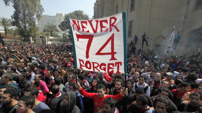 An Egyptian soccer fan of Al-Ahly club raises a banner honoring fellow fans killed in a 2012 stadium riot in the club headquarters in Cairo, Egypt, Saturday, March 9, 2013. An Egyptian court on Saturday confirmed the death sentences against 21 people for taking part in a deadly soccer riot but acquitted seven police officials for their alleged role in the violence. Suspected fans enraged by the verdict torched the soccer federation headquarters and a police club in Cairo in protest. (AP Photo/Amr Nabil)