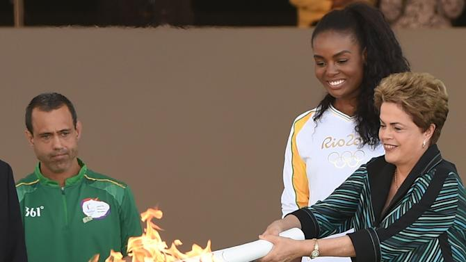 Brazilian President Dilma Rousseff (R) hands the Olympic torch to volleyball player Fabiana Claudino at Planalto Palace in Brasilia following the flame's arrival in Brazil on May 3, 2016