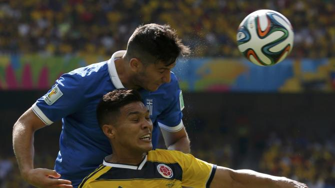 Greece's Kostas Manolas fights for the ball against Colombia's Teofilo Gutierrez during their 2014 World Cup Group C soccer match at the Mineirao stadium in Belo Horizonte