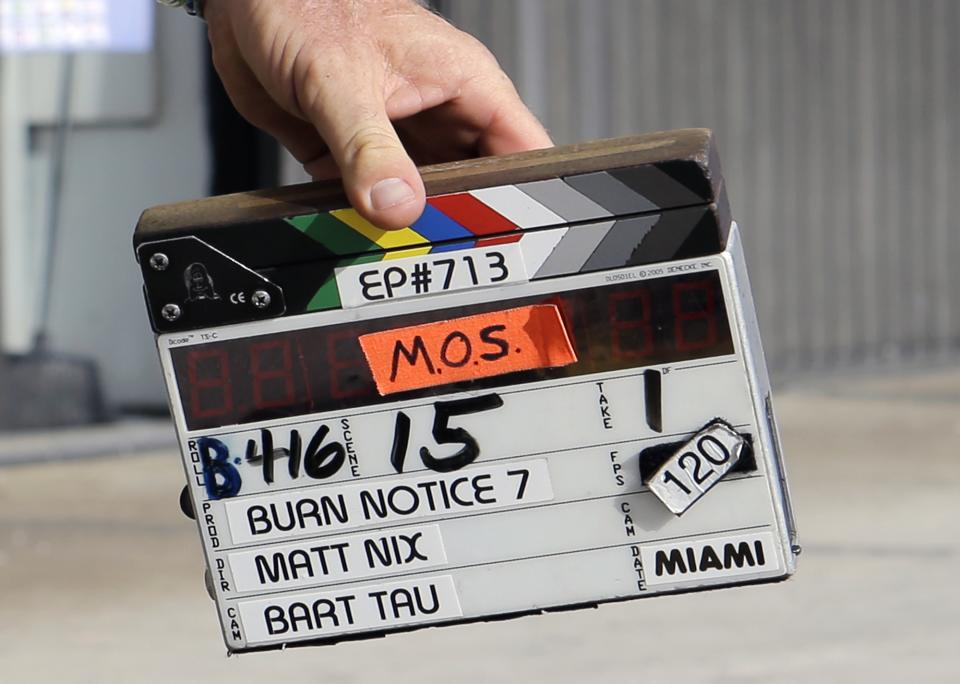 "This July 24, 2013, photo shows a clapperboard during taping for an episode of ""Burn Notice"" in Miami. The cable spy drama is coming to an end after seven seasons with a big finale next Thursday, Sept. 12, 2013. (AP Photo/Alan Diaz)"
