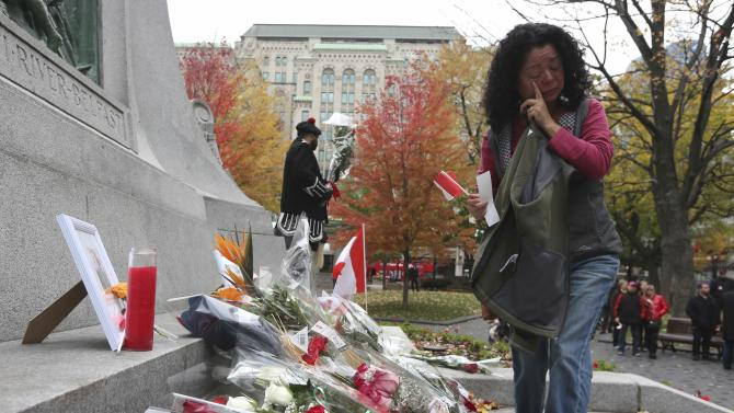 A woman wipes away tears as she places flowers for fallen Canadian soldiers, Warrant Officer Patrice Vincent and Corporal Nathan Cirillo, during a vigil in Montreal