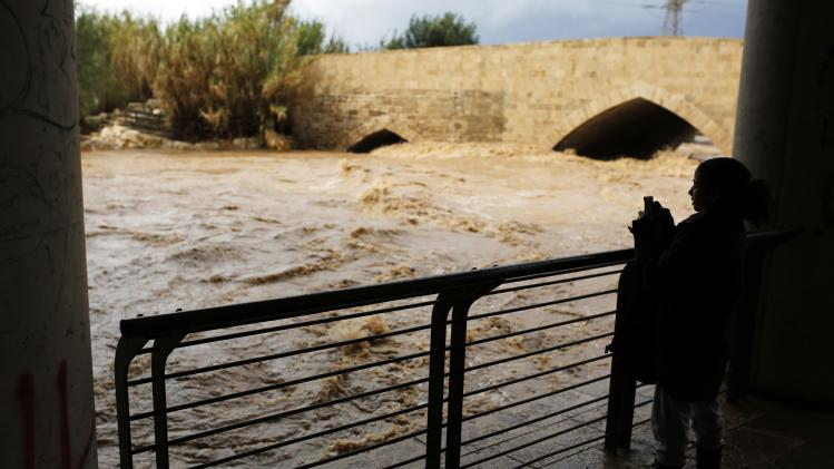 A girl takes a photo of a flooded river due to heavy rains near Ashdod