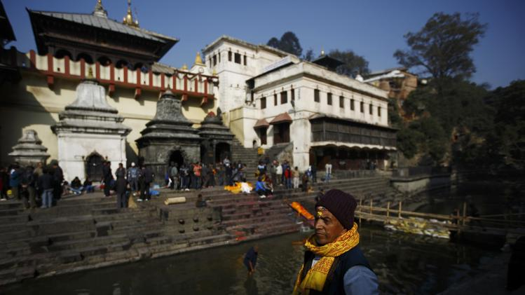 A priest stands near the banks of the Bagmati River at Pashupatinath Temple in Kathmandu