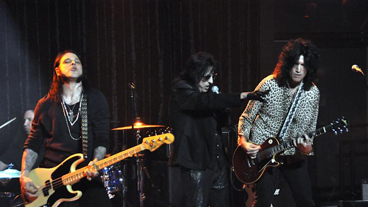 "Alice Cooper, center, sings his song ""Under My Wheels"" with bassist Chuch Garric, left, and guitarist Tommy Thayer of Kiss, Thursday, March, 28, 2013, at a concert benefiting the Brennan Rock & Roll Academy in Sioux Falls, S.D. (AP Photo/Dirk Lammers)"