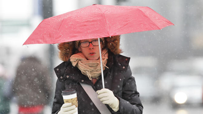 A woman uses an umbrella during a storm that brought some snow and a fast plunge in temperature overnight to downtown Denver, Tuesday April 9, 2013. The storm has so far proved less potent than originally predicted in Colorado because the cold front lingered in Wyoming. Up to around 10 inches of snow had fallen in Colorado's mountains by dawn Tuesday. Another 5 to 10 inches was possible in some locations but final snowfall amounts would vary quite a bit, National Weather Service forecaster Jim Daniels said. (AP Photo/Brennan Linsley)