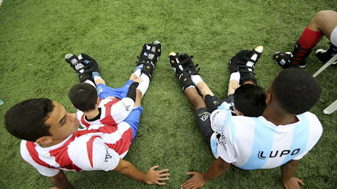 "Disabled children Gabriel and Caua, partnered with Brazilian soccer players Gontijo and Arthur, take a break during the ""World Boots"" event for children with disabilities, at the Neymar Institute in Praia Grande"
