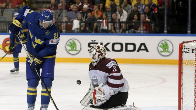 Sweden's Eriksson challenges Latvia's goaltender Masalskis during their Ice Hockey World Championship game at the O2 arena in Prague