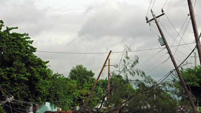 A fallen tree and toppled light poles block a road in Kingston, Jamaica, after the passing of Hurricane Sandy, Thursday, Oct. 25, 2012. Sandy, which made landfall Wednesday afternoon near Kingston, crossed over Jamaica killing an elderly man when a boulder crashed into his clapboard house, police said. (AP Photo/Collin Reid)