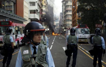 Riot police guard a street where a fire was set by protesters at Mongkok district in Hong Kong