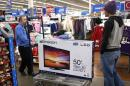 "A Walmart employee helps a customer with a 50"" TV on sale for $218 on Black Friday in Broomfield"