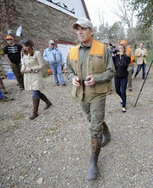 FILE - In this Oct. 22, 2011, file photo, Republican Presidential candidate, Texas Gov. Rick Perry walks to a truck before a hunting trip near Merrill, Iowa.  They are fuzzy about some issues but the Republican presidential candidates leave little doubt about where they stand on gun rights. Democrats have learned the hard way that embracing gun control can be terrible politics, and the 2012 presidential election is shaping up to underscore just how delicate the issue can be. With the election likely to be decided largely by states where hunting is a popular pastime, like Missouri, Ohio or Pennsylvania, candidates of both parties want to win over gun owners, not alienate them.  (AP Photo/Dave Weaver, File)