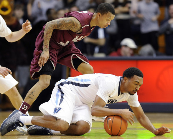 Villanova&#39;s Darrun Hilliard, right, dives on a loose ball in front of Saint Joseph&#39;s Carl Jones during the second of an NCAA college basketball game, Tuesday, Dec. 11, 2012, in Villanova, Pa. Villanova won 65-61. (AP Photo/Michael Perez)