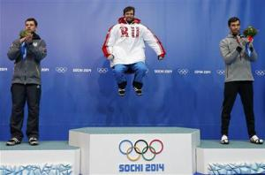 Winner Russia's Tretiakov jumps on the podium between second-placed Latvia's Martins Dukurs and third-placed Antoine of the U.S. after the men's skeleton event at the 2014 Sochi Winter Olympics