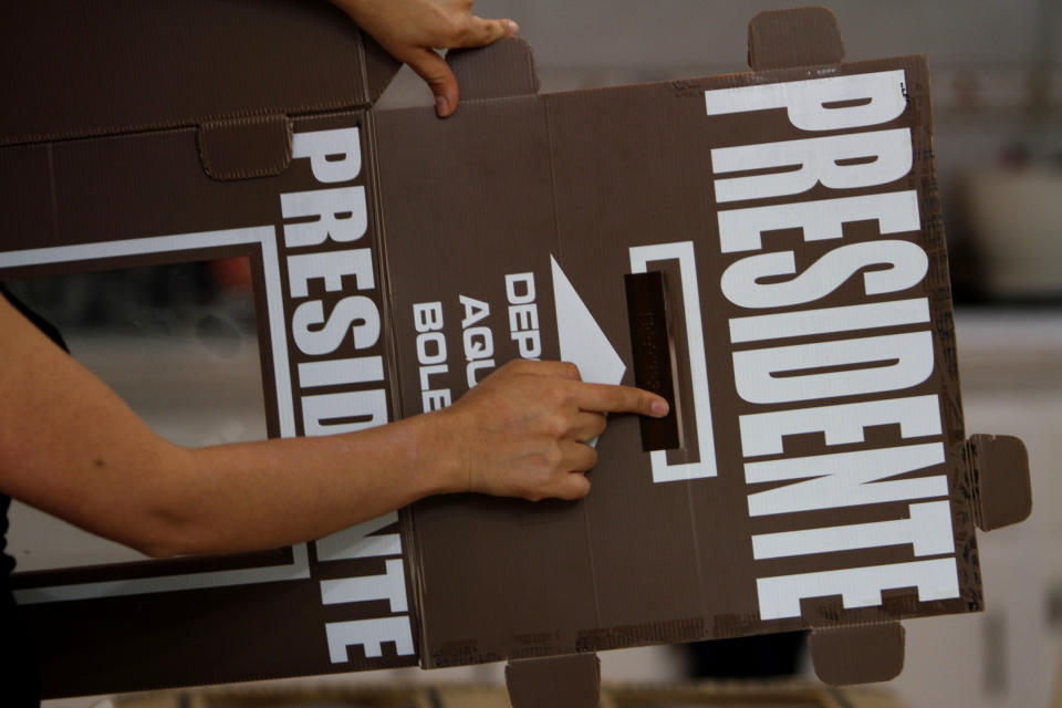 Election worker Ninel Ramirez Torillo shows a box that will be used to hold ballots for the upcoming presidential election in Mexico City, Saturday, June 30, 2012. Mexico will hold general elections, including the presidential election, on July 1.  (AP Photo/Marco Ugarte)