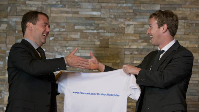 Russian Prime Minister Dmitry Medvedev, left, shakes hands with Facebook CEO Mark Zuckerberg at the Gorki residence outside Moscow,  Russia, Monday, Oct. 1, 2012. Zuckerberg presented Medvedev with a T-shirt bearing his Facebook address. (AP Photo/Alexander Zemlianichenko, pool)