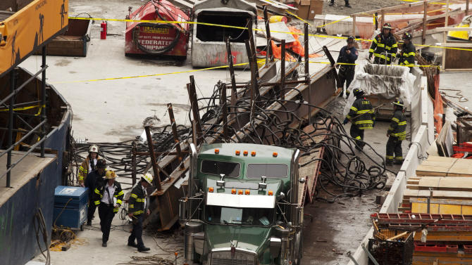 Firefighters inspect a load of steel beams and broken cable that fell onto the back of a truck at the World Trade Center construction site, Thursday, Feb. 16, 2012 in New York. Preliminary reports indicate that a crane atop Four World Trade Center was unloading the beams from the truck when the cable snapped, dropping the beams onto the truck. No one was seriously injured in the accident. (AP Photo/Mark Lennihan)