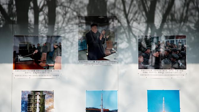 "Trees are reflected on a board displaying photos of North Korean leader Kim Jong Un and the country's successful long range rocket launch outside North Korean embassy in Beijing Tuesday, Feb. 12, 2013. North Korea apparently conducted a widely anticipated nuclear test Tuesday, strongly indicated by an ""explosion-like"" earthquake that monitoring agencies around the globe said appeared to be unnatural. There was no confirmation from Pyongyang that it had conducted a test, which it has been threatening for weeks. (AP Photo/Andy Wong)"