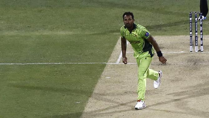 Pakistan's Wahab Riaz watches as Zimbabwe's captain Elton Chigumbura hits a catch and is caught out for 35 runs to end their Cricket World Cup match at the Gabba in Brisbane
