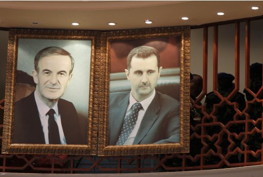 Members of the UN observers mission in Syria are seen near portraits of Syrian President al-Assad and his late father in Damascus
