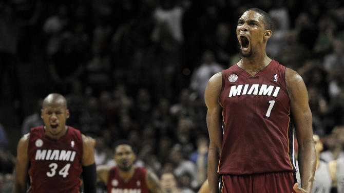 Miami Heat's Chris Bosh (1) yells after scoring the winning basket during the second half of an NBA basketball game against the San Antonio Spurs, Sunday, March 31, 2013, in San Antonio. Miami won 88-86. (AP Photo/Darren Abate)