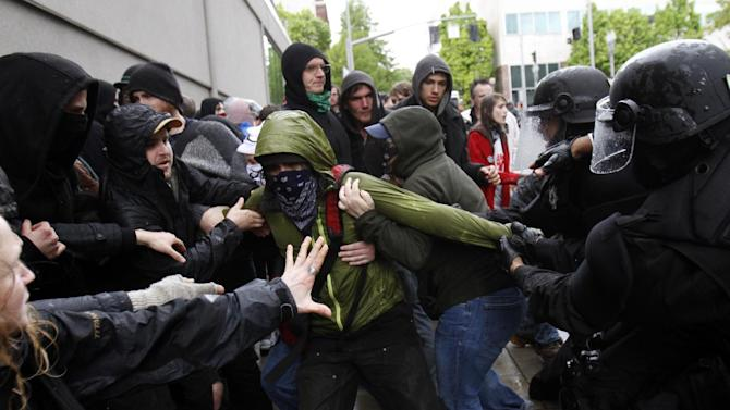Violence erupts during a May Day march and protest in Portland, Ore., Tuesday, May 1, 2012. Up to 100 protesters set out on an unpermitted march late Tuesday morning. Some got off the sidewalk and into the street. Police on horses and bikes tried to push them back onto the sidewalk, and a shoving match ensued. (AP Photo/Don Ryan)