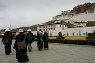 File photo of Tibetans passing the Potala Palace in the Tibetan capital Lhasa. Residents of Lhasa say the city is under even tighter security than usual following Sunday's protest, in which two men set themselves on fire, with police and paramilitary officers out in force